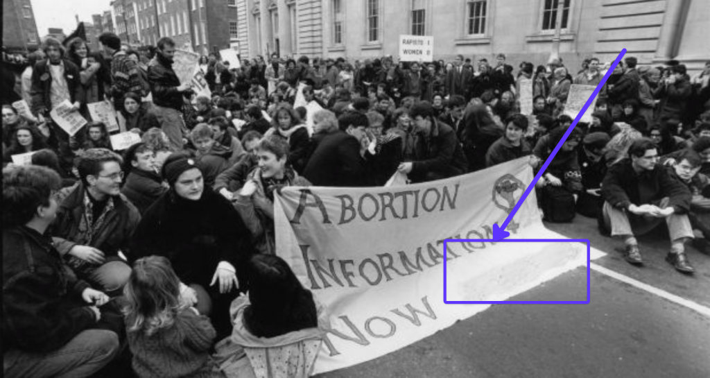 Students from 1992 sitting in the road in the Dail, behind a banner saying 'Abortion Information Now'. A highlighted square and arrow draws attention to where the image has been altered to cover up a phone number.