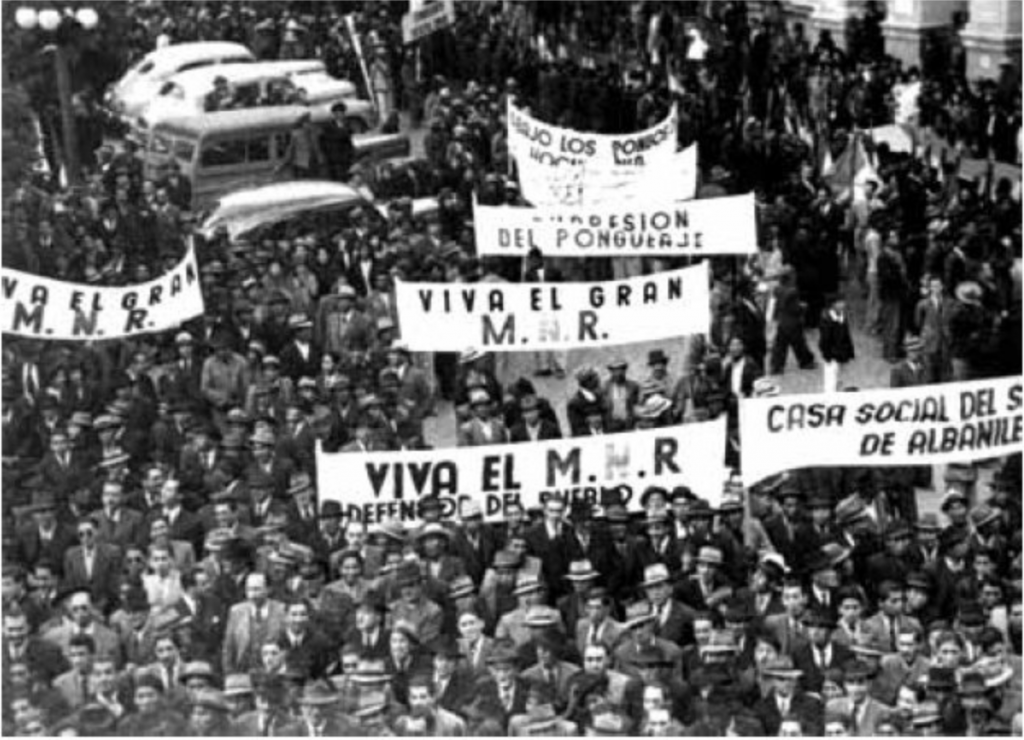 Bolivia 1952, massive crowds of workers march behind white banners, the most prominent of which reads VIVA EL M.H.R.