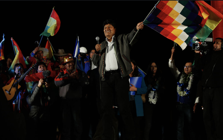 Evo Morales waving the colourful flag of the Movement Towards Socialism against a black, night-time background. He is smiling and so are the people around him, some of whom also wave flags and others have musical instruments.