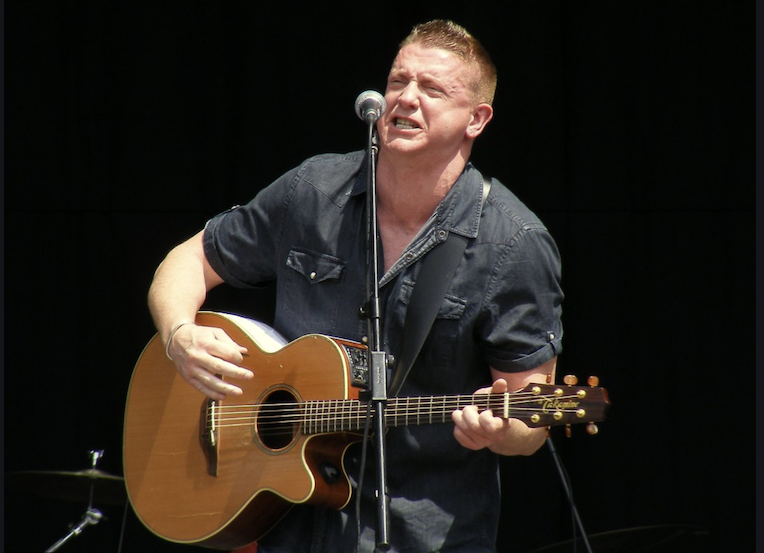Damien Dempsey, wearing a black shirt and shitting in front of a microphone holding a guitar. His expression of one of intense feeling.