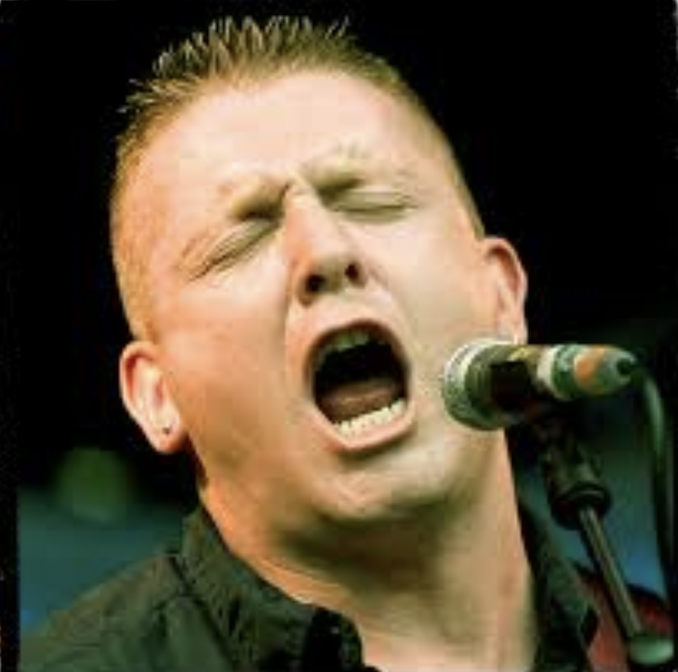 Close up of Damien Dempsey singing open-mouthed before a microphone, eyes closed with an intense expression.