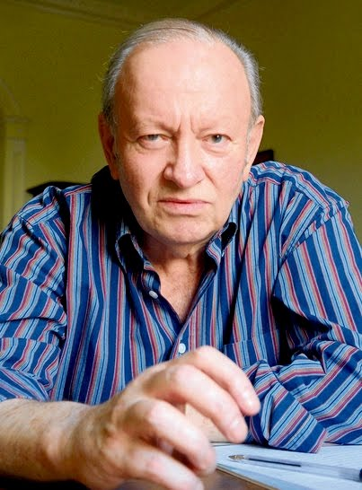 A portrait of Derek Mahon, poet, who describes himself as having a penchant for left-wing imagery. He is wearing a blue and purple vertical stripped shirt and is looking directly at the camera with a slight smile.