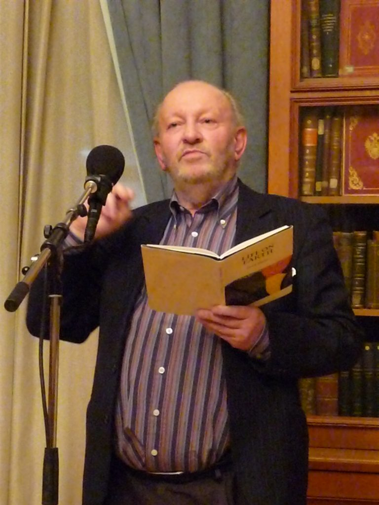 Radical poet Derek Mahon reading from a book of his own poems held open in his left hand. His right is raised. He is smiling. A microphone is in front of him and behind him are curtains and the end of a bookcase  or cabinet with finely bound books.