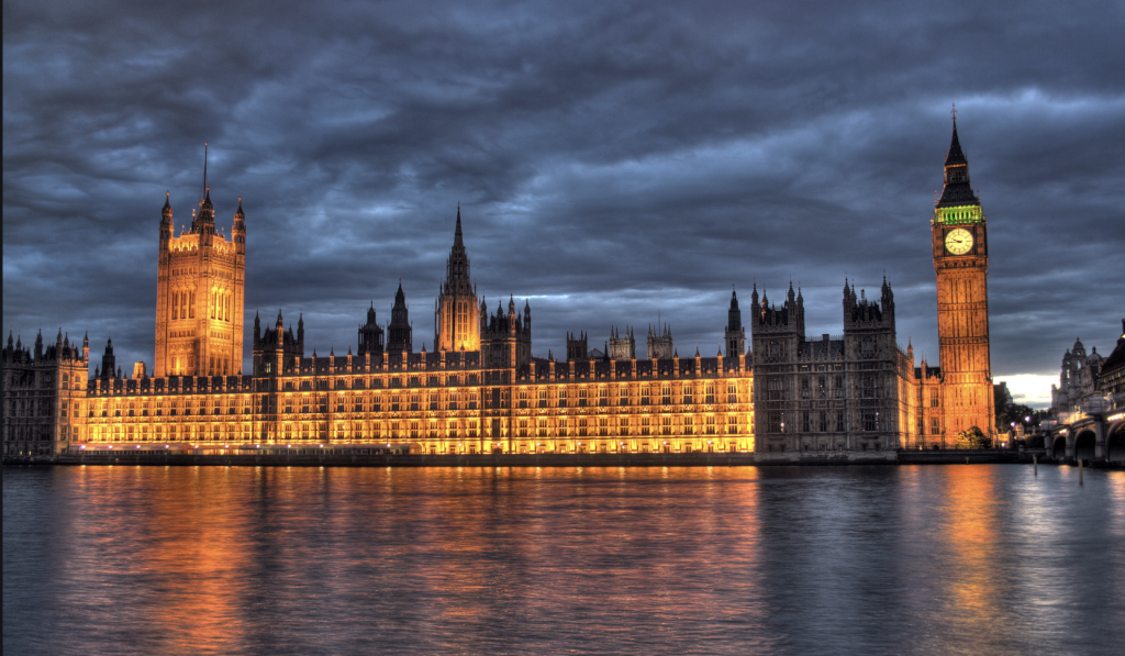 A picture of Westminister Parliament from the south bank of the Thames, it is just after sunset and the building is lit up with yellow and orange light reflected on the water. This is where the Tory part will hold a majority in the light of the 12 December 2019 general election.