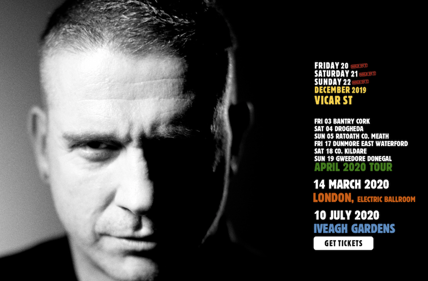 The left hand side of the image shows a striking, black and white portrait of Damien Dempsey, with a slight smile. On the right are tour dates: December 2019 ones in Vicar Street (the venue in yellow letters); a space then a block of six dates in April (green) 03 Bantry, 04 Drogheda. 05 Ratoath, 17 Dunmore East, 18 Co. Kildare, 19 Gweedore. Then a space and 14 March 2020 Electric Ballroom London (orange) and 10 July 2020 Iveagh Gardens (blue).