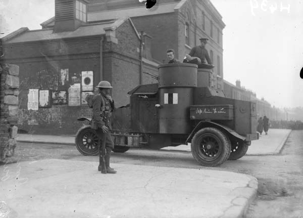 A black and white picture taken during Ireland's biggest general strike, showing a British soldier standing to attention beside an early-looking armoured car, which seems to be a truck with a circular body adapted for defence. Two soldiers are emerging from the centre of the vehicle.