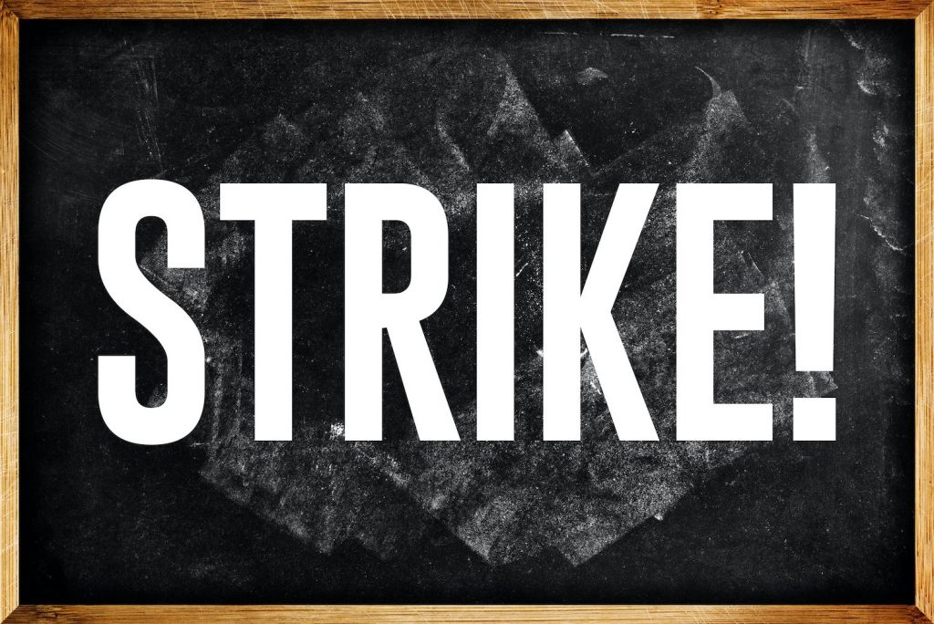 A blackboard with thick white letters saying: STRIKE! Teachers will be on strike 5 February 2020.