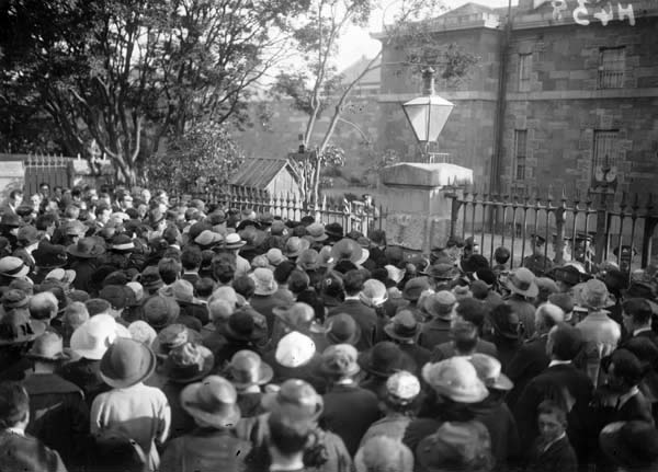 A side street near Mountjoy Prison (background) is filled with people looking away from the camera towards the bared windows of the prison. This was the situation on Monday 12 April 1920 when the biggest general strike in Irish history took place.