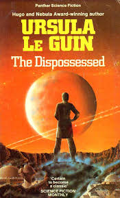 The first edition cover of The Dispossessed by Ursula Le Guin. Her name is at the top in large yellow letters, then, smaller, the title in white. The entire background is orange with a figure of ambiguous gender silhouetted against a large orange planet, facing away from the reader, standing in a crater. In this novel, Le Guin began with the premise of an anarchist utopia.