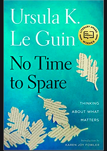 The turquoise cover of No Time to Spare, a collection of blog essays written by Ursula Le Guin, which include her thoughts on socialism. Five leaves made of paper with illegible writing on them are drifting towards the bottom of the cover.