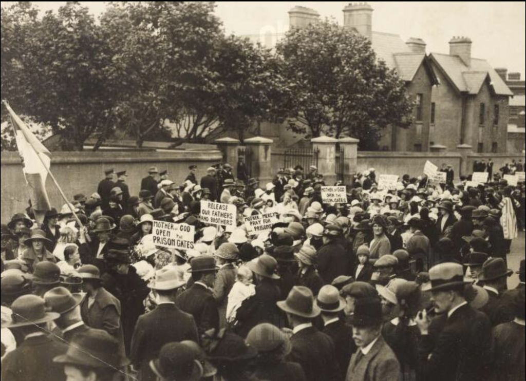 A large number of women fill a street near the Mountjoy Prison. One of them is holding a tricolour. Many of them have placards reading 'Mother of God Open the Prison Gates'. A small number of police look on from beside a wall on the far side of the crowd. Black and white, taken in April 1920 during Ireland's biggest general strike.