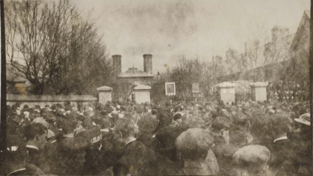 A sepia photograph of a large crowd in front of the gates of the Mountjoy Prison. All are facing away from the camera and most are men wearing cloth caps. Taken in April 1920 during Ireland's most radical general strike.