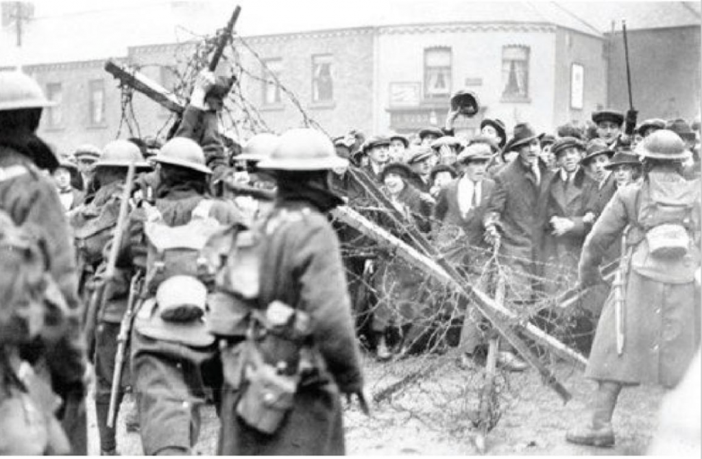 A faded photograph taken outside the Mountjoy Prison during Ireland's great general strike of 1920. In the foreground are five British soldiers with characteristic Great War gear, including bowl-shaped helmets. They are facing away from the camera at crowd of civilians with animated expressions. Between them is a construction of wood and barbed wire.