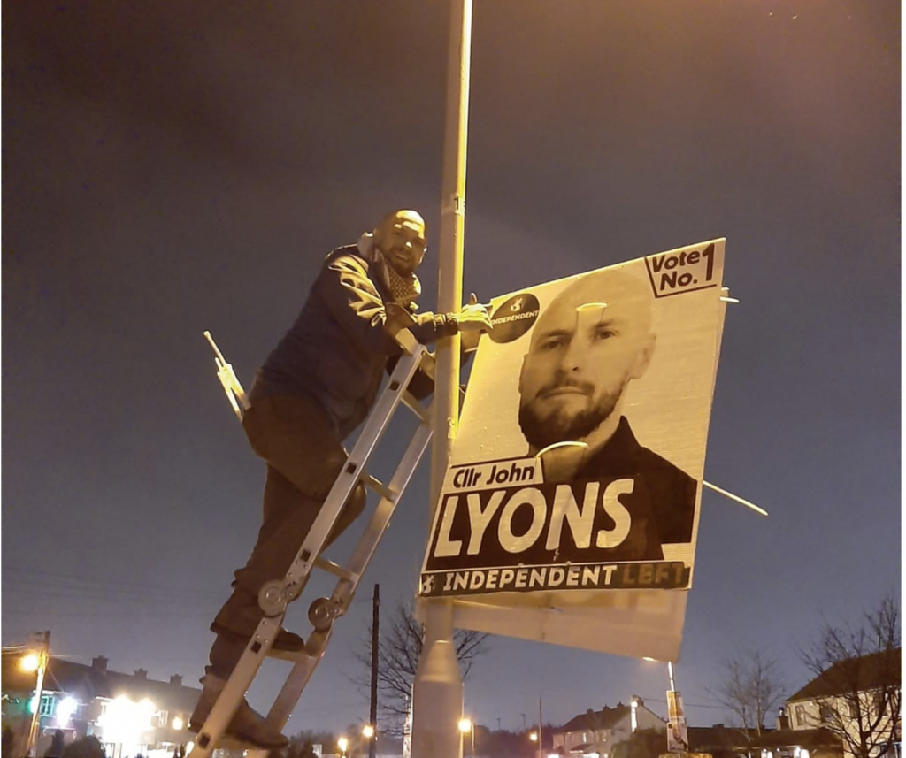 Councillor John Lyons running for election in Dublin Bay North, pictured in the evening on a ladder, smiling as he lifts a post with a large poster of his head and shoulders, on which is written Vote No.1, Cllr John Lyons, Independent Left.