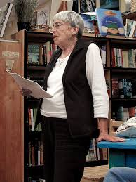 Ursula Le Guin in 2008. She has short, grey hair, a white top, black tunic and trousers. Her left hand on a table, her right holds several A4 pages and she is speaking against a background of books. Ursula Le Guin was sympathetic to socialism.