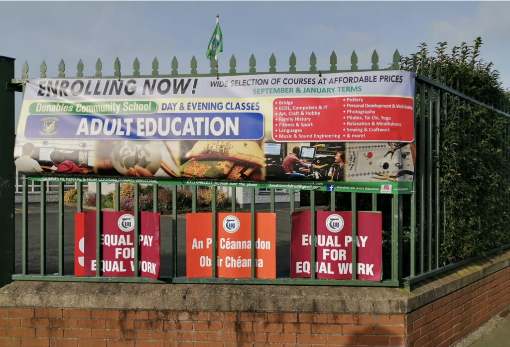 A railing with a banner: Enrolling Now! Day and Evening Classes. Adult Education at Donahies Community School. Below the banner are three TUI placards placed by teachers striking on 4 February 2020.