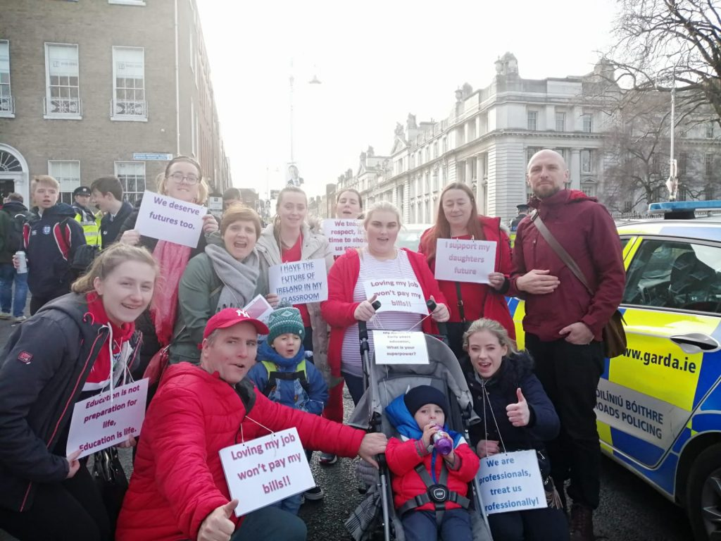 John Lyons of Independent Left stands on the right of a group of childcare workers and parents at the demonstration of 5 February 2020. The demonstrators display a lot of red clothing and have placards around their necks proclaiming: loving my job won't pay my bills! We are professionals, treat us professionally.
