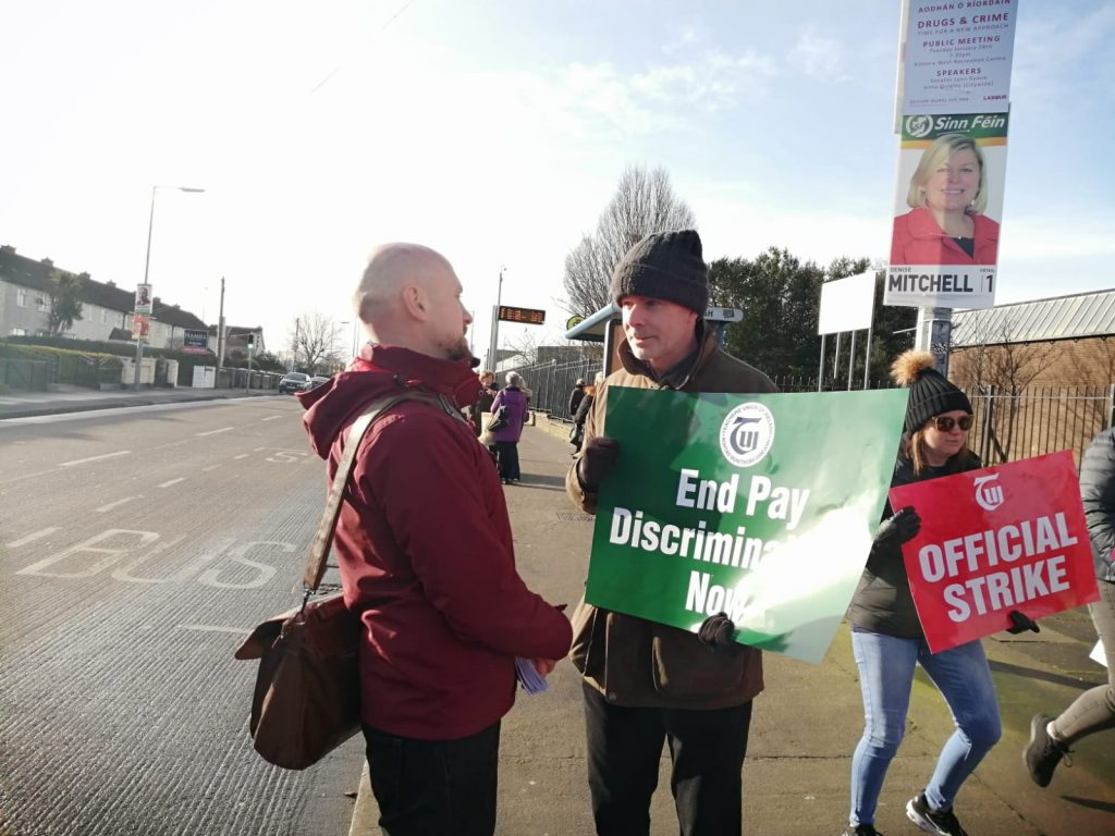 Councillor John Lyons joining the pickets at Coláiste Dhúlaigh during the strike of 4 February 2020. John Lyons is on the left, a male teacher is talking to him on the right, holding a green placard with white writing: end pay discrimination now. Behind him a female teacher is mid stride with a red placard and white writing: TUI OFFICIAL STRIKE.