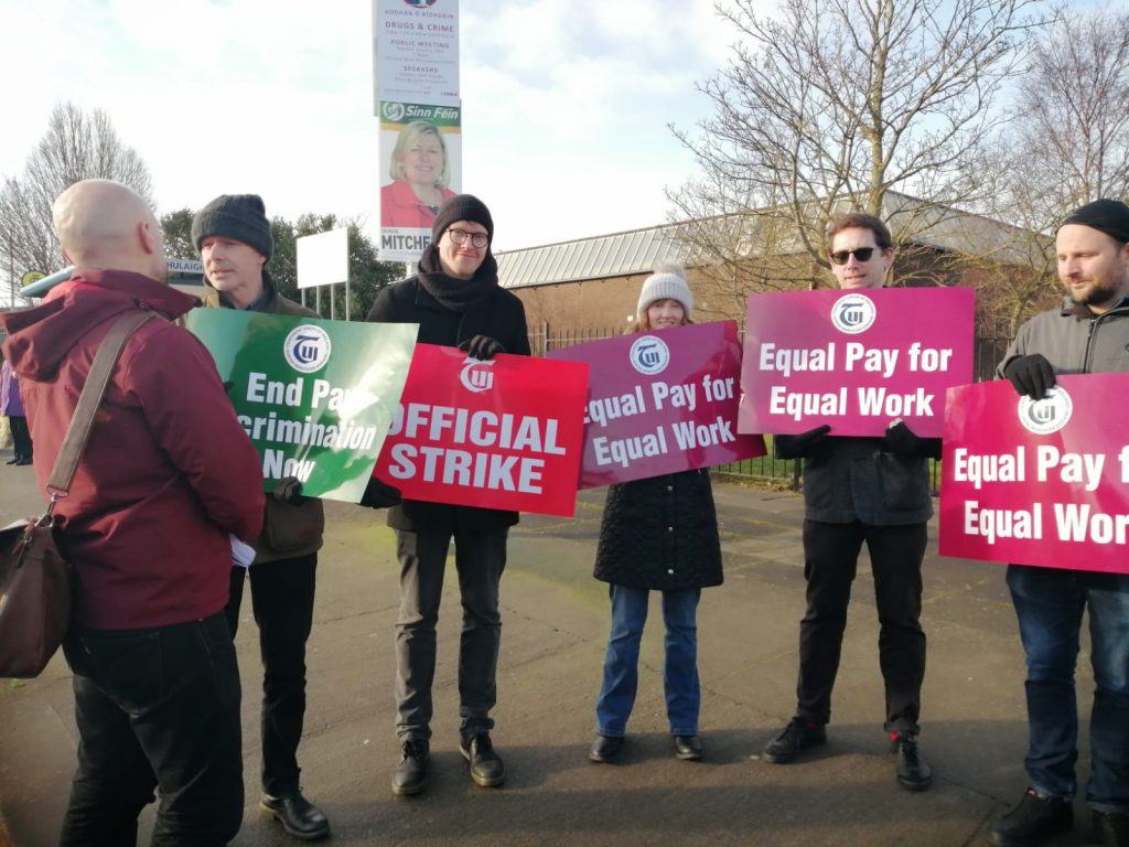 Councillor John Lyons talking to TUI pickets outside of Coláiste Dhúlaigh during the strike of 4 February 2020. John Lyons is on the left of the picture. Five teachers in thick coats and wearing wooly hats are holding placards: End Pay Discrimination Now, TUI Official Strike, Equal Pay for Equal work.