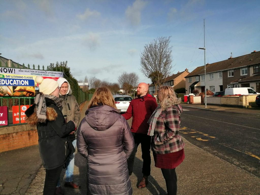 TUI members at Donahies Community School talking to Councillor John Lyons on the day of their strike for equality in pay, 4 February 2020. Three women teachers and one man in thick jackets are stood in a circle around Councillor John Lyons who is gesturing. Behind them is a wall with a railing on which is a banner for day and evening classes at Donahies Community School.