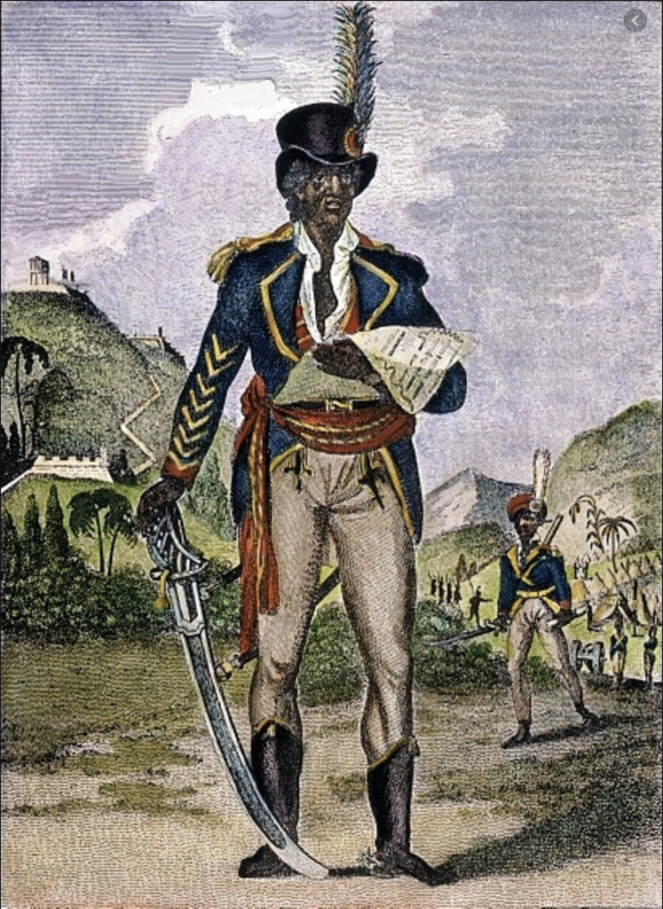A nineteenth century colourised engraving of Toussaint L'Ouverture, the revolutionary former slave who helped the successful slave revolt of 1791 achieve independence for Haiti. He stands in a uniform similar to that of a French contemporary officer, but with a straight hat with a feather in it. In his right hand, a sabre is drawn, tip resting on the ground. In his left if a proclamation.