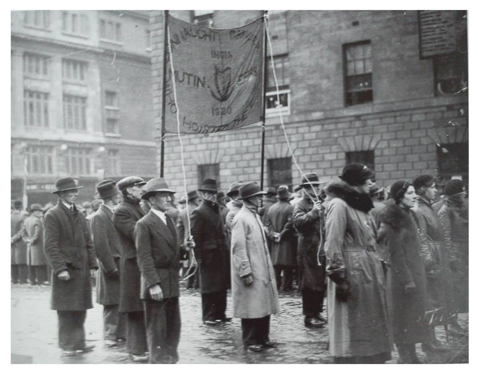 A black and white photograph of a parade outside the GPO, O'Connell Street Dublin, probably taken in 1936. Underneath a banner that reads Connaught Rangers mutiny are seven men in long coats and pulled down hats. In front of them are a row of four women also in long coats and hats. The men were participants in the Connaught Rangers mutiny of 1920.
