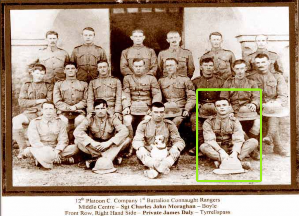 A sepia-tinged photograph of 12th Platoon, C Company 1st Battalion Connaught Rangers. Four men sit on the ground in the front row (the second from right having a dog in his lap), eight are seated in the middle row and six men stand at the back. Highlighted in a green box is the young man, front row right hand side. This is Jim Daly, leader of the mutiny at Solon in 1920.