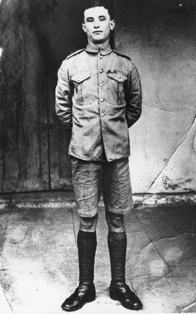 A black and white picture of a young soldier in a uniform that has shorts. He seems to be smirking at the camera. This is a full length portrait of Jim Daly, the republican to whom the rebels at Jullundur looked to spread their mutiny to Solon.