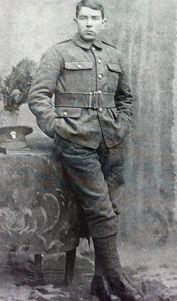 Jim Hawes, one of the initial instigators of the Connaught Rangers mutiny is shown in a full length black and white portrait. He wears the uniform of the Munster Fusiliers, his peaked hat resting on a table against which he leans, hands in pockets, a nonchalant expression on his face.