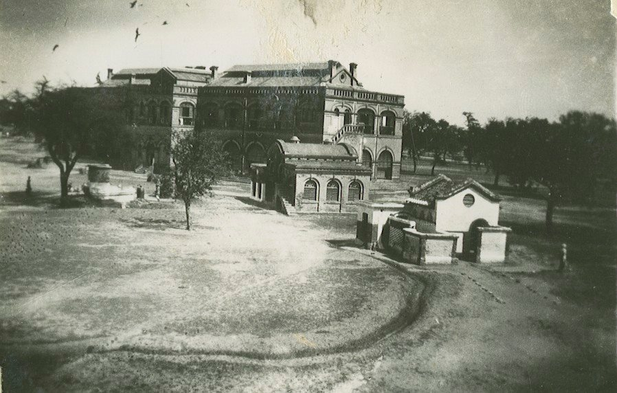 A black and white picture of a large parade ground with a very big building at the top of the picture. It is Jullundur barracks and has two floors, arched decorations around the windows and a triangular roof.