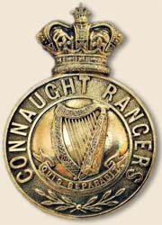 Brass badge with a crown on top of a circle. Around the circle are the words Connaught Rangers and in the centre a harp.
