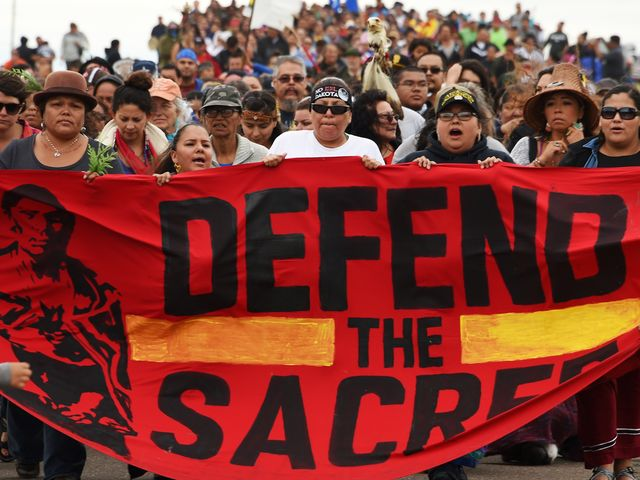 A red banner fills the bottom half of the image with the words: Defend the Sacred. Holding it are members of the Sioux community and behind them a crowd. The issue concerns the Dakota Access pipeline, North Dakota.