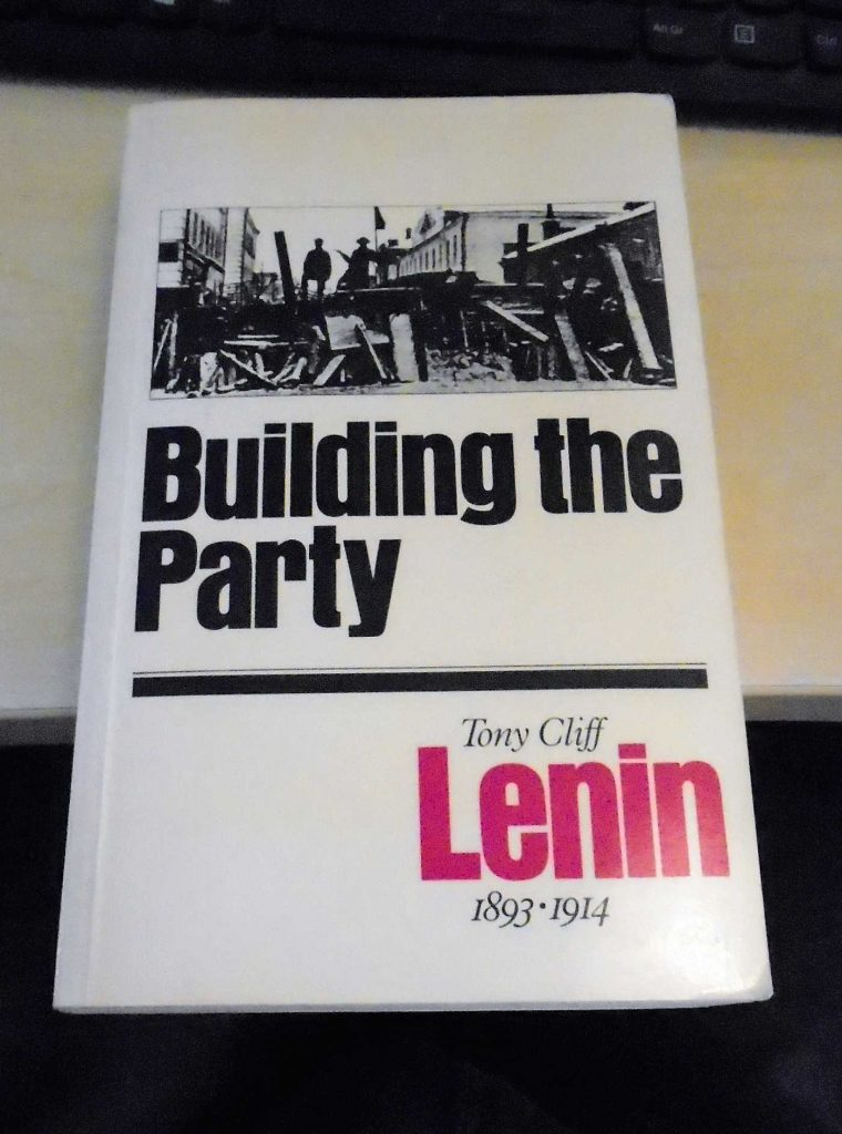 A photo of the jacket of the 1986 edition of Tony Cliff's Lenin: Building the Party (Bookmarks). The title is in thick black letters across the middle of a white cover, beneath a picture of a barricade taken during the 1917 revolution. The word Lenin is in mauve, in. the bottom right corner.