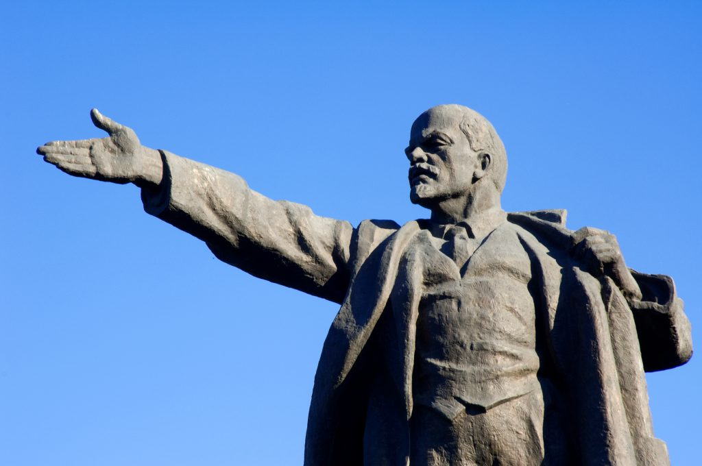 A clear, deep blue sky against which is a sunlit statue of Lenin, pointing to the viewer's left, palm open. His own left hand hold's the lapel of his coat for balance and his expression is determined. A 1954 Communist vision of Lenin.