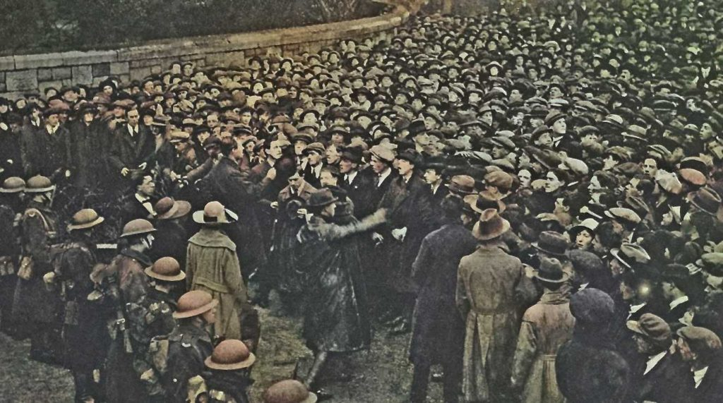 A colourised newspaper image of a huge crowd (on the right) facing a row of British soldiers (on the left). A narrow space exists between them with a row of men (and one woman) in civilian clothes but with leather jackets, facing the crowd.