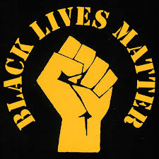 Black Lives Matter logo. A yellow image on a black background. A stylized left hand is clenched in a fist, around which like a halo is written: Black Lives Matter in an old 'zine font.