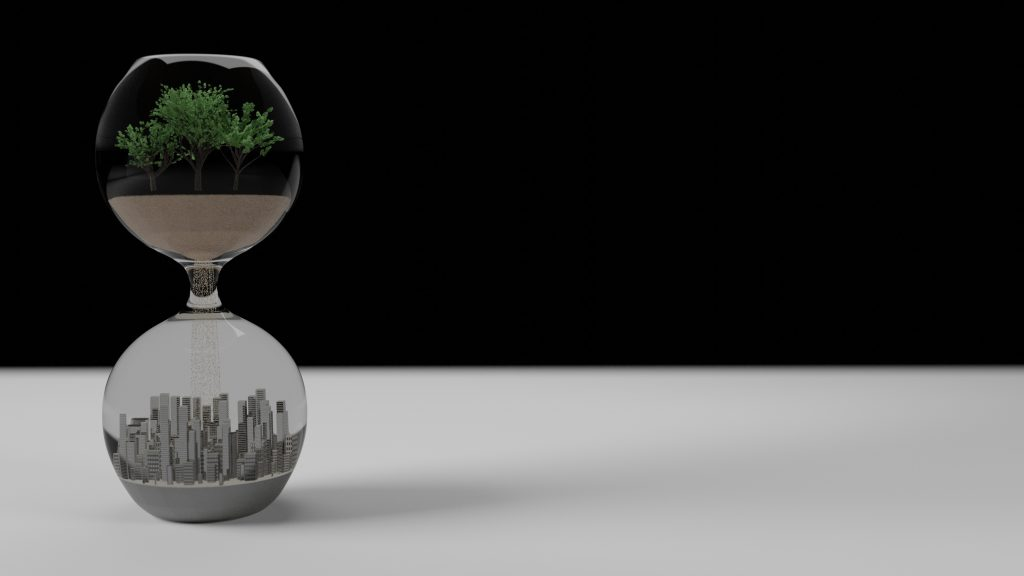 A glass sand timer stands on the left of the image against a stark black background, resting on a white table. Inside the top half of the glass is a miniature tree in sandy soil. Underneath is the skyline of a modern city. The image evokes an impending collapse of the web of life by capitalism.