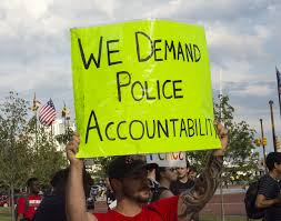A protestor holds up a green banner on which is written: We Demand Police Accountability.
