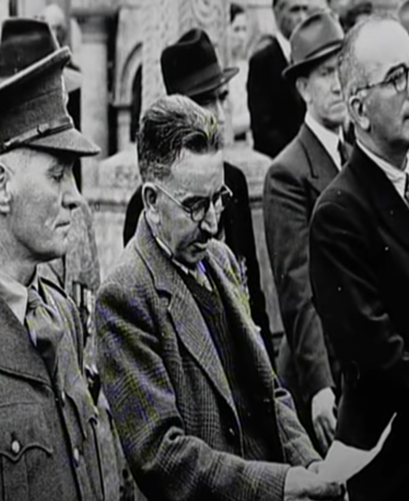 In 1970, a commemoration took place in Glasnevin cemetery for those who participated in the mutiny of the Connaught Rangers. Pictured is an elderly Joe Hawes, wearing glasses, looking down at a piece of paper from which he is delivering his oration. An army officer in uniform is on the left of the image and is glancing down at Joe's notes.
