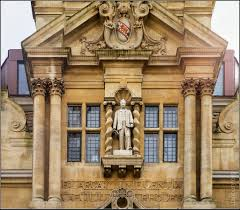 High above the entrance to the Rhodes Building, Oriel College Cambridge is a statue to Cecil Rhodes. The image shows Rhodes in white stone against a yellow stone building with four lead-lined rectangular windows either side of him.