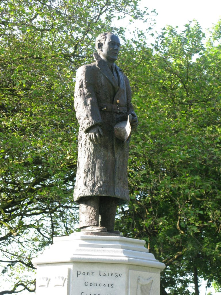 Bronze statue of Seán Russell, Fairview Park, Dublin. Russell is in a long coat and holding a hat in his left hand. He is on a plinth, facing to the viewer's right. Green trees fill the background.