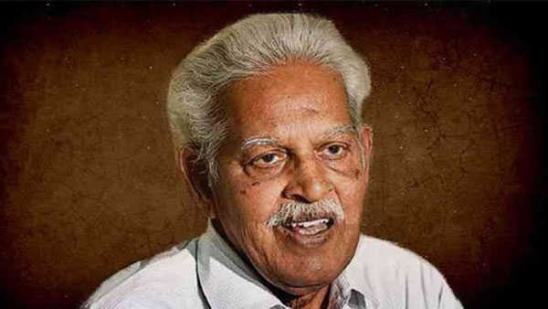 Varavara Rao pictured against a brown and amber wall. He is grey-haired, grey-moustached and is smiling, looking at someone to the right of the camera. Taken before his imprisonment in 2018, he is in good health.